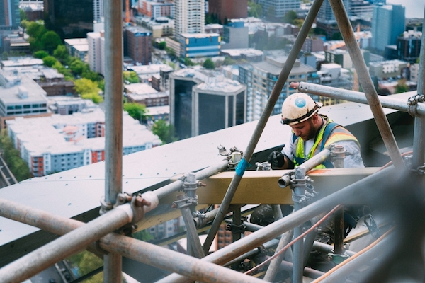 Construction Worker Working with Steel and Wood on a Skyscraper